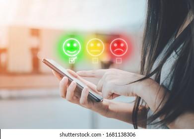 Erfahrung im Kundendienst und Umfrage zur Unternehmenszufriedenheit. Nahaufnahme von weiblichen Händen mithilfe von Smartphone wählen Sie Gesichtslächeln aus