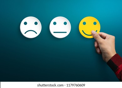 Customer service experience and satisfaction survey concepts. The client's hand picked the happy face smile face.