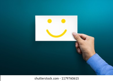 Customer service experience and satisfaction survey concepts. The client's hand holding the card with a happy face smile face.