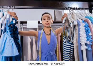 Customer service. Inspired female sale assistant touching clothes and looking at camera
