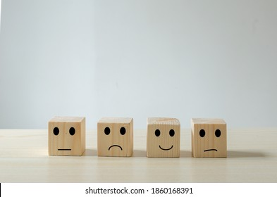 Customer service ratings and feedback emotion concept wood cube.satisfaction survey with negative, neutral and positive facial expressions