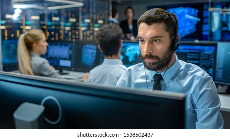 Customer Service Representative Answer Client's Questions in a Headset. He Works for a Big Technological Company. Office Has Multi-Ethnic Team of Specialists, Displays Show Useful Information.