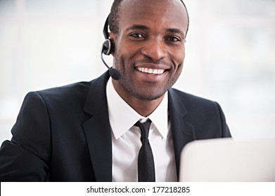 Customer service representative. Cheerful young African man in formalwear and headset working on laptop and smiling at camera