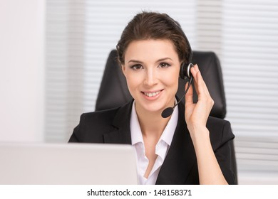 Customer service representative. Confident middle-aged woman in headphones sitting at her working place and smiling