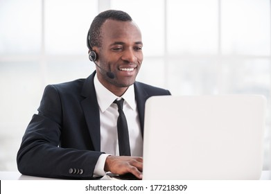 Customer service representative at work. Cheerful young African man in formalwear and headset working on laptop and smiling