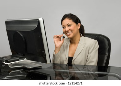Customer service / sales representative with a headset looking at a monitor