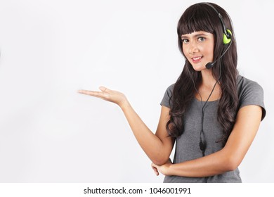 customer service woman with headphone hand pointing. Confident customer service representative. Beautiful young female customer service representative in headset holding her hand blank space