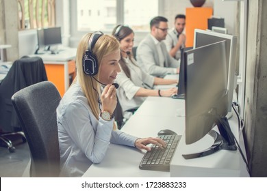 Customer services agents with headset working in a call center. - Shutterstock ID 1723883233