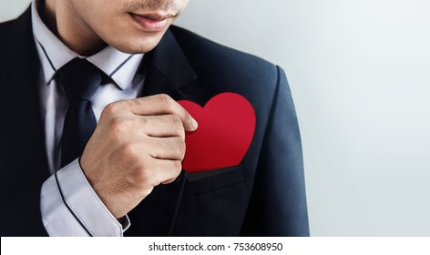 Customer Services Concept, Businessman Dropping a Heart (paper card) in his Pocket with Carefully
