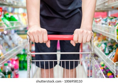 Customer with shopping cart choosing product in supermarket