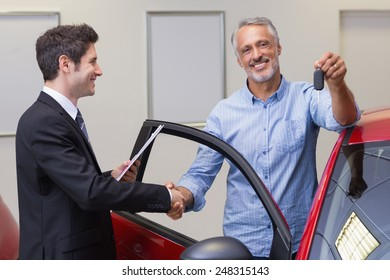 Customer showing his new key while shaking a hand at new car showroom