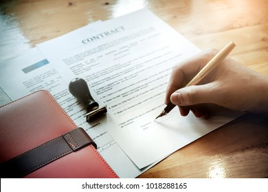 customer sign contract and pressing rubber stamp on house contract document. Agreement concept.