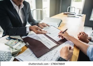 Der Kunde unterzeichnet Vertragsunterlagen für den Immobilienkauf, die Mitarbeiter der Bank beglückwünschen, Genehmigung des Hypothekarkredits. Geschäftsdarlehen eines Bankangestellten. Finanzierungskonzept .