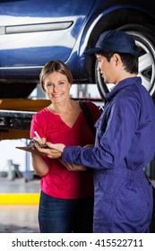 Customer Signing Document While Standing With Mechanic