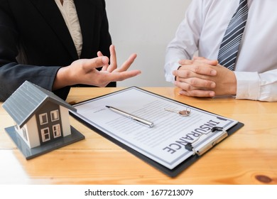 Customer signs the house insurance contact after listening the contact agreement from agent, Finance, Insurance concept.