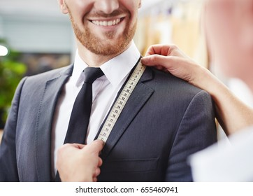 Customer smiling to camera during model fitting of bespoke quality suit