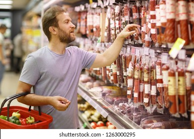 Customer standing in meat section and choosing salami or sausages. Bearded man holding basket and looking at meat assortment. Concept of buying food in supermarket and gastronomy.
