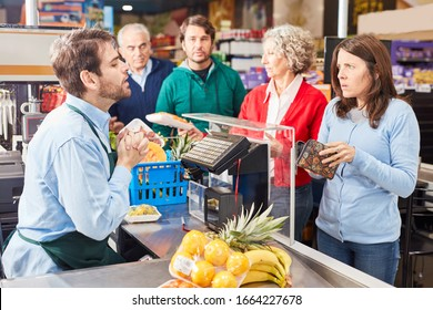 Customer at the supermarket cashier has too little money in the wallet for shopping