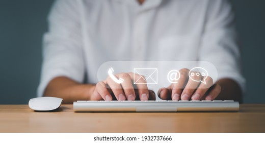 Customer support hotline Contact us people connection. Businessman using computer keyboard with the email, call phone, address, Chat message icons.