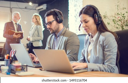 Customer support operators working on laptops in office. Focus on businessman with headset.