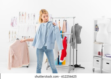 Customer tries new clothing collection of a successful fashion designer in her showroom