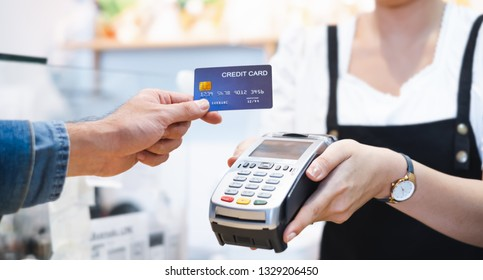 Customer using credit card for payment to owner at cafe restaurant, cashless technology and credit card payment concept