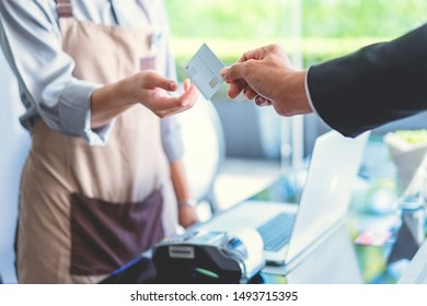 Customer using credit card for payment at coffee shop.