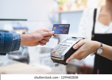 Customer using credit cart for payment to owner at cafe restaurant, cashless technology and credit card payment concept