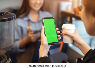 Customer using her smartphone and nfs high technology to pay a barista for her purchase with phone, mobile payment, online shop at coffee cafe.