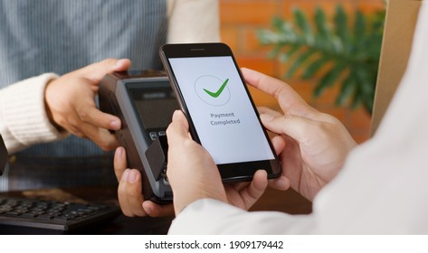 Customer using phone for payment at cafe restaurant, cashless technology and money transfer concept