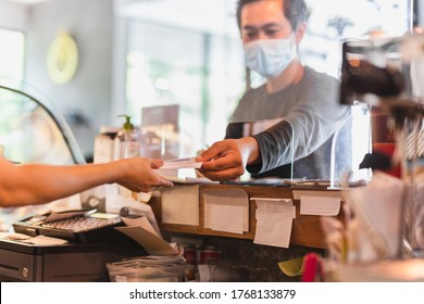 Customer wearing protective mask paying bill at counter with partition shield.