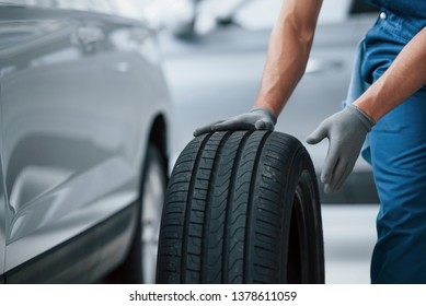 Customer will not wait. Mechanic holding a tire at the repair garage. Replacement of winter and summer tires.