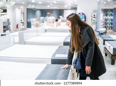 Customer woman buying new furniture - bed in a store supermarket mall store