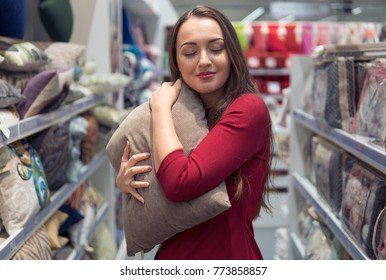 Customer woman chooses bed linen and bed in the supermarket mall store. She is hugging pillow with tenderness
