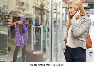 Customer woman in shopping street, looking at window, outdoor