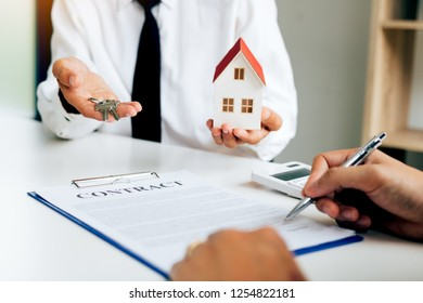 Customer writing signing signature on paper contract with real estate agent and giving key to client.