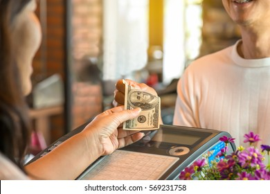 Customer young man and woman cashier holding money with smiling face, bokeh blurred background,business concept.Pay with cash at register.