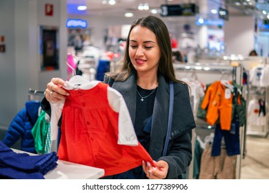 Customer young woman choosing baby clothes or children's wear in the shop. Buying in the store for infant kids