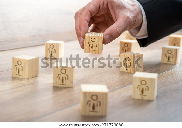 Kundenverwaltetes Beziehungskonzept - Geschäftsmann, der kleine Holzblöcke mit Symbolen auf dem Tisch anbietet.