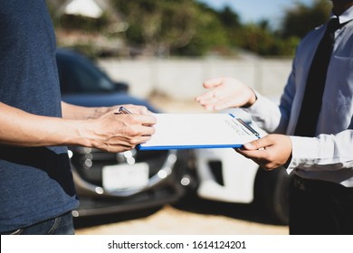 Customers and car insurance agents have entered into agreements and signed documents to claim compensation after a car crash, Insurance concept.