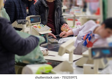 Customers at cash desk with cashier in supermarket