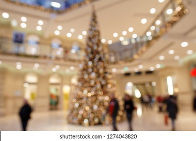 Customers in Christmassy Shopping Mall in Front of Christmas Tree