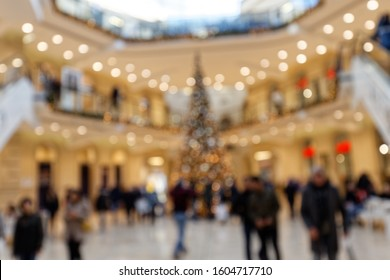 Customers in Christmassy Shopping Mall in Front of Christmas Tree Blurred Background