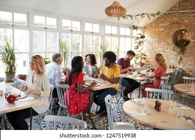 Customers eating at a busy restaurant in the day time