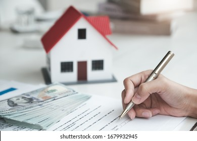 Customers are reading loan and insurance agreement documents to sign real estate transactions.