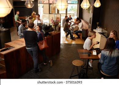 Customers waiting at counter in a busy modern coffee shop