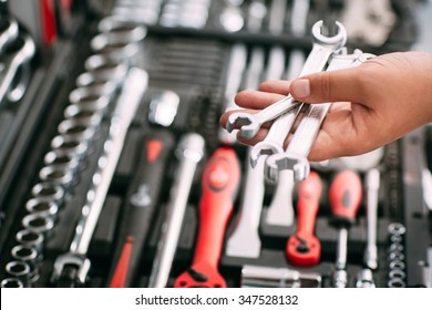Customers or worker (builder, repairman, handyman) at the store chooses wrench instrument (tools). Display of tools shop marketing for home and auto repair