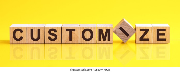 customize word written on wood block. customize word is made of wooden building blocks lying on the yellow table. customize, business concept, yellow background