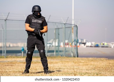 Customs and border protection officer and Drug enforcement administration special force participates in a training at the airport for searching and seizing of illegal drugs. Unrecognizable people.