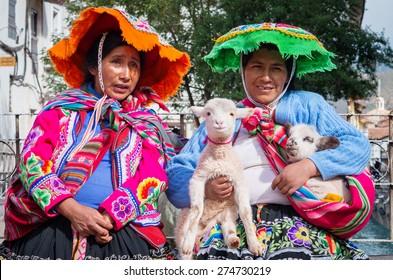 CUSZO, PERU - MARCH 18, 2015: Peruvian woman in traditional dresses pose  for tourists in Cuzco, Peru